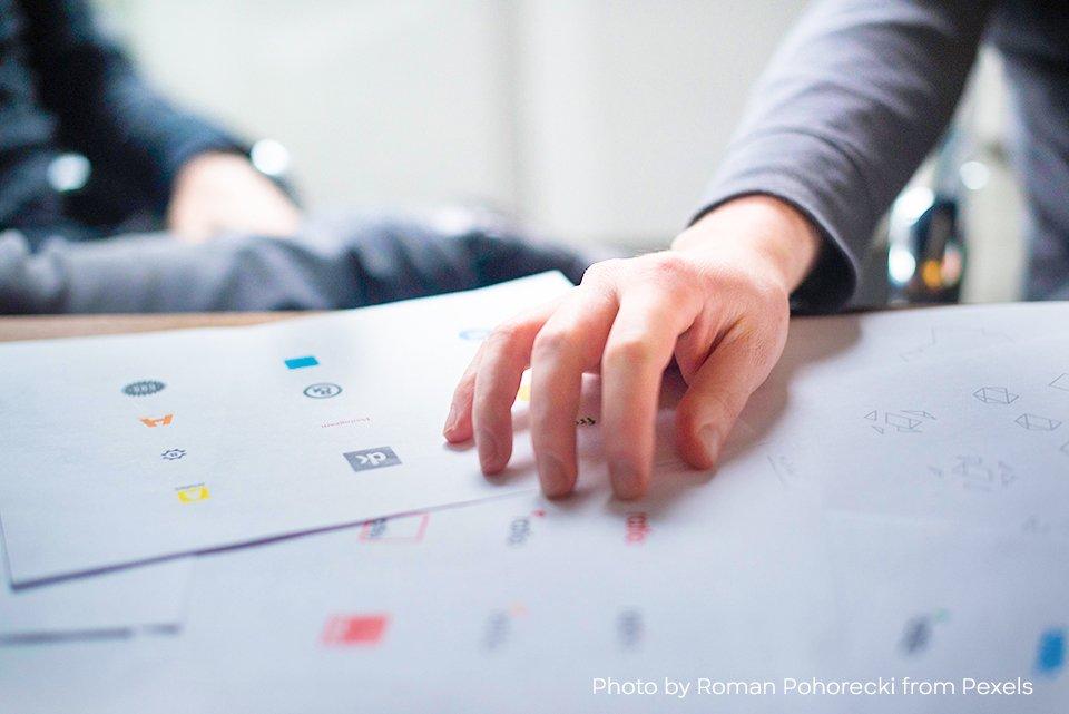 mano de hombre sobre papeles que contienen graficos, sobre un escritorio que cierra la conclusion de Cómo crear tu logo en 5 etapas