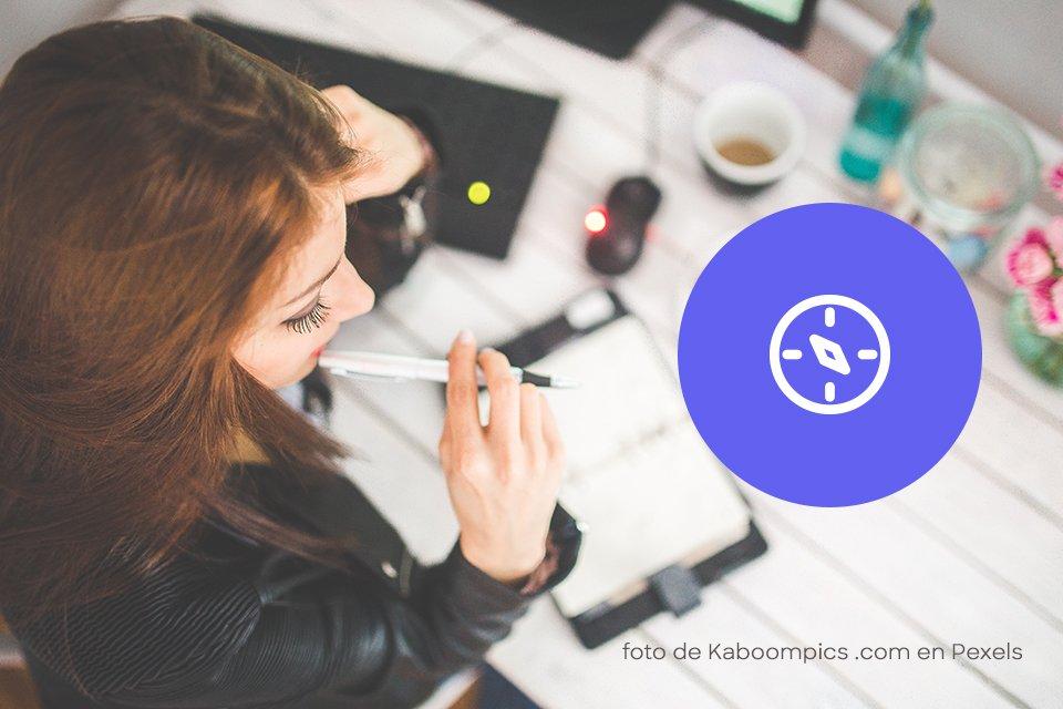 mujer joven pensando sobre escritorio y pluma en la boca y botón azul morado etapa descubrir de Cómo crear tu logo en 5 etapas