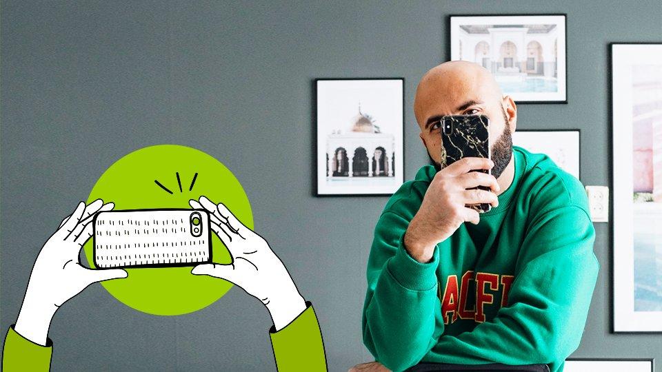 hombre tomando una foto con su smarthphone, sudadera verde, movil
