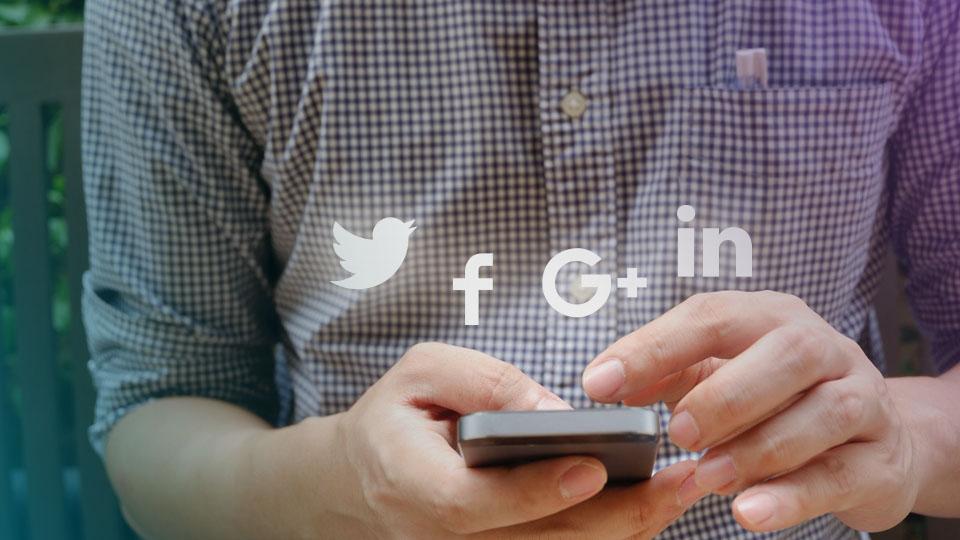 Celular en mano con logos holográficos de redes sociales
